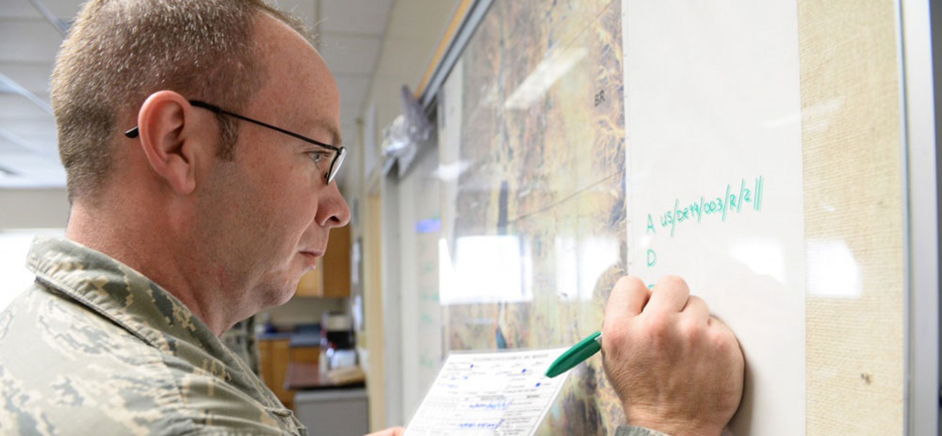 Military student writing on whiteboard